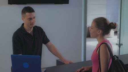 two people wearing sportswear talking near reception desk. Mixed race man explaining information about new services in sport club.