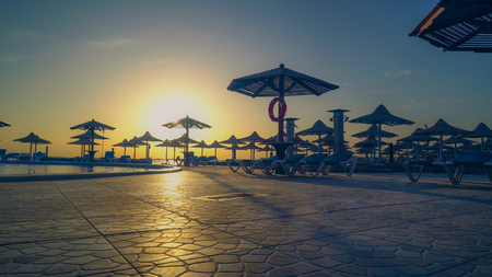view on the beach with outdoor furniture at early morning. pool without people in hotel rising of the sun. Stock Photo