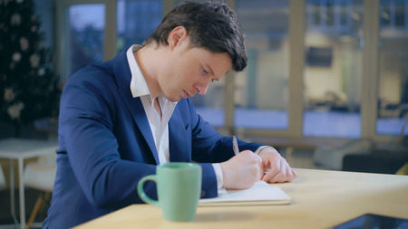 Caucasian male hand writing notes in notebook. Handsome man sitting at the wooden desk colored cup with desk. young businessman planned to do list.