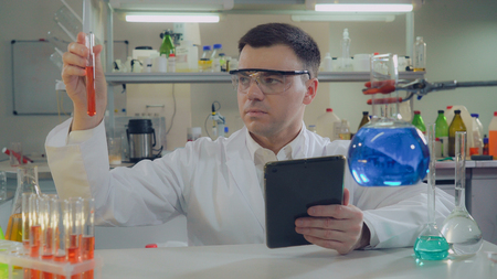 middle aged scientist working in chemical laboratory. Man wearing white coat using digital tablet.