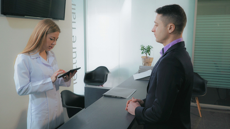 Adult man in dental clinic or in hospital standing in lobby talking with receptionist . Blonde woman greeting male using computer check patient admission time or make an appointment.