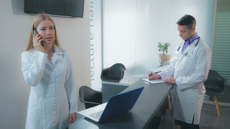 Caucasian nurse or doctor s assistant using telephone has phone conversation with patient. Adult doctor standing near reception desk fill documents in clinic.