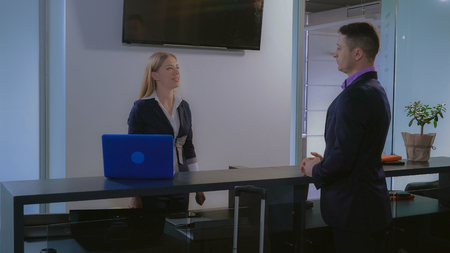 visitor giving passport to receptionist in hotel. Beautiful caucasian worker entering information on computer check booking. Businessman with suitcase standing near reception desk. Mixed race man wearing suit in business trip.