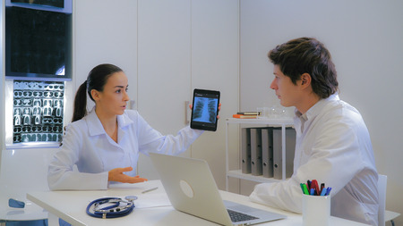 Young doctor consults with a colleague. Woman asking advice about patients x-ray. Adult man looking on tablet touch screen with scan of lungs and talking with female. Collaboration two doctors in hospital. Stok Fotoğraf