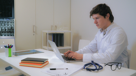Handsome caucasian therapist typing on laptop in office. Man wearing white coat focused looking on screen pc. On the desk x-ray phonendoscope and eyeglasses.