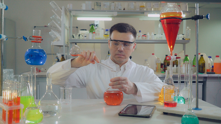 Adult doctor working in microbiological or chemistry or medical laboratory. pouring liquid to glass bulb. Caucasian man wearing in white coat and eyeglasses working alone in lab. Stock Photo