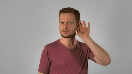 caucasian guy with red hair posing showing hand gesture puts his hands to ear and listening. handsome redhead men wearing in casual t-shirt. portrait young caucasian man on grey background Stok Fotoğraf
