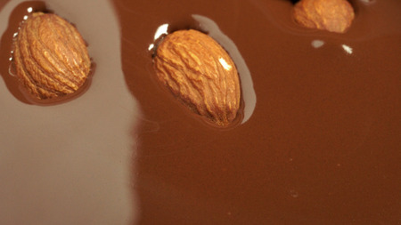 Almonds fall into melted chocolate.
