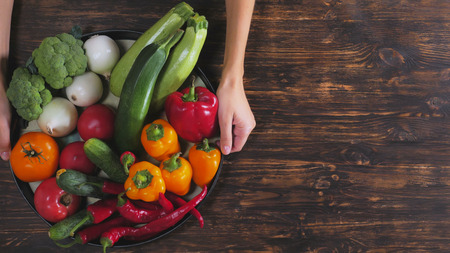 Unrecognizable woman holding tray different season vegetables over the wooden table. Close up female hands with pepper, broccoli, zucchini, cucumber, zucchini, tomato, onion Stock Photo