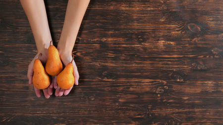 Unrecognizable woman holding fruits over the wooden table. Close up female hands with orange pears