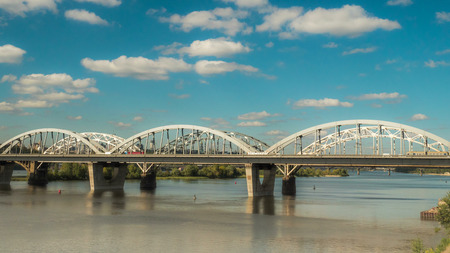 The movement of clouds over the bridge along which cars and trains are moving, a river flows under the bridge, and early autumn has come. Stock Photo