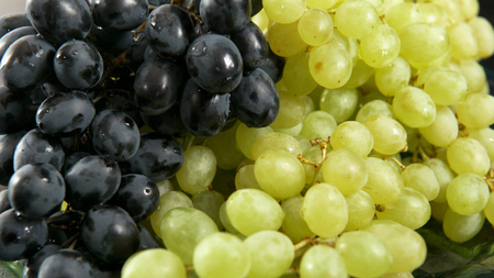 Green and blue bunch of grapes lying on a platter. Stock Photo - 117836307