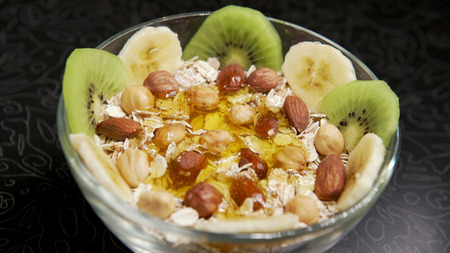 Pouring honey oatmeal with fruit and nuts.