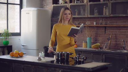 domesticity in modern life. Adult woman cooking and reading book with recipe on kitchen. Businesswoman wearing in casual elegant dress at home standing near cooker stir slowly soup.