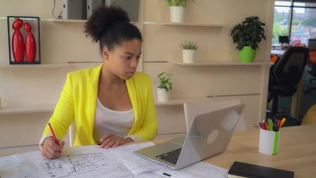 Mulatto mixed race woman at work wearing in casual yellow jacket. Banco de Imagens