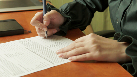 Woman signs a contract. Signature. Stock Photo