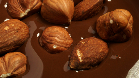 Hazelnuts and almonds fall into the melted chocolate. Stock Photo