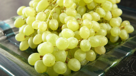 Green bunch of grapes lying on a platter. Stock Photo - 117836371