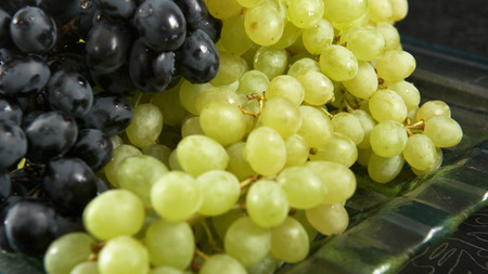 Green and blue bunch of grapes lying on a platter. Stock Photo