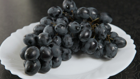 Blue bunch of grapes lying on a platter. Stock Photo