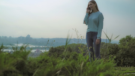 A young girl with long dark hair standing on a hill high grass and talking on the phone.