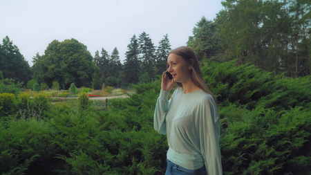 A young girl goes green summer park and talking on the phone, smiles, rejoicing.