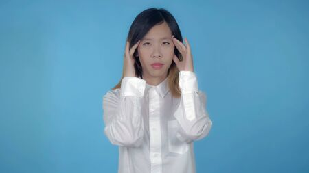 young asian happy woman posing has headache or migraine on blue background in studio. attractive millennial girl wearing white casual shirt looking at the camera Archivio Fotografico