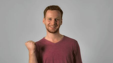 happy caucasian guy with red hair celebrate success. handsome redheaded men wearing in casual t-shirt. Portrait ginger young caucasian man on grey background