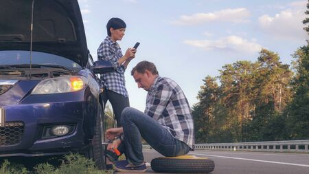 handsome caucasian man changing a tire on the side of the road. Woman using mobile phone messaging or scrolling social media on smartphone .