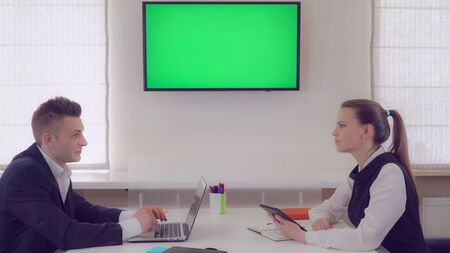 Business partners discussing project. Adult workers sitting in office on wall monitor with green screen. Coworkers using digital device wearing uniform.
