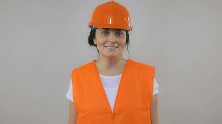 happy beautiful caucasian woman with black hair wearing hard hat and orange uniform posing in studio. Portrait young girl wearing casual white t-shirt