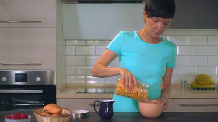 Adult caucasian woman pouring milk in bowl with cereals. Brunette eating fast healthy breakfast in the kitchen. women wearing blue casual t-shirt relish her meal.