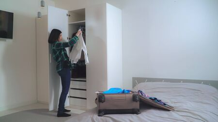 Young happy woman packing male and female clothes in suitcase. Smiling brunette planning traveling in apartment with casual interior.
