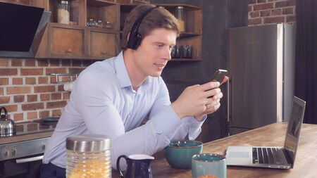 Happy smiling businessman listening new song using headphones. Cheerful man enjoy breakfast and favorite playlist in the kitchen at home. Caucasian model wearing casual clothes holding smartphone. Archivio Fotografico