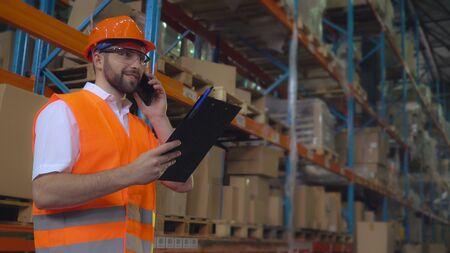 Portrait manager at work in warehouse has phone conversation with client. Handsome worker talking by smartphone discussing the logistics. Man wearing hard hat and orange vest Archivio Fotografico