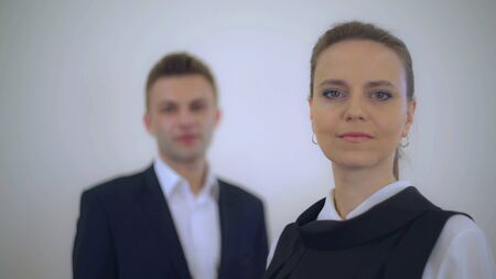portrait business partners posing looking at the camera. Adult businessman and businesswoman wearing formal clothing white and black color. Focus defocus.