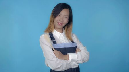 young asian woman posing with spoon wearing like cook on blue background in studio. attractive millennial girl wearing white casual shirt looking at the camera smiling.