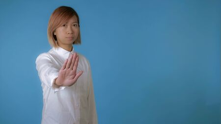 portrait young asian female posing showing hands gesture stop on blue background in studio. attractive korean woman with blond hair wearing white casual shirt looking at the camera