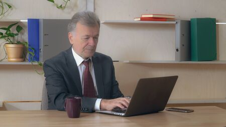 Man in years typing on computer in office. Middle aged male wearing in elegant suit. Stock Photo
