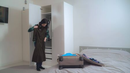 Lady try on dress and put it in suitcase. Young woman wearing in casual clothes packing bag planning vocation. Caucasian girl with black hair in apartment.