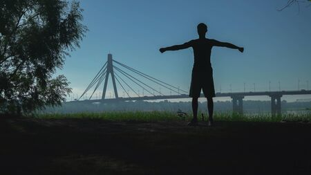A silhouette of a young man performing exercises circular rotations hands at the open air. In the background bridge with cars. Guy warming up arm do morning stretching. Athlete listening music with earphones on smartphone. Urban view in summer season sunrise. Archivio Fotografico