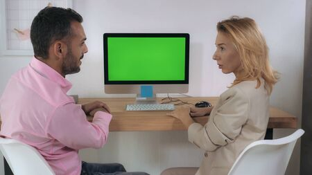 Business negotiation in office. Handsome professional man giving presentation showing on computer with green display. Caucasian blonde adult woman looking on screen pc listens attentively and showing interest Archivio Fotografico