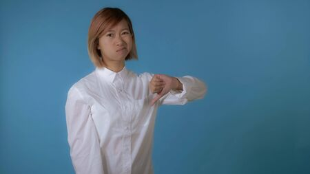portrait young asian female posing showing sign like and dislike on blue background in studio. attractive korean woman with blond hair wearing white casual shirt looking at the camera Archivio Fotografico