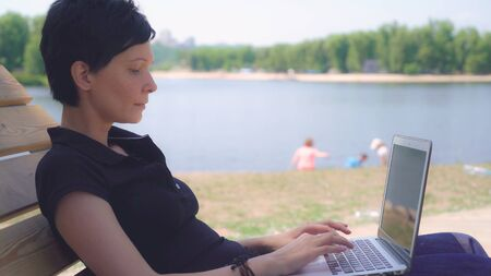 Brunette using laptop outdoors. Adult woman resting near lake in summer season typing on computer. Young businesswoman working or chatting or messaging in social net on the beach. Female with short black hair wearing casual polo shirt.