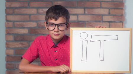 Portrait little boy showing whiteboard with handwriting word it. Child with spectacles on smart face. Preadolescent wearing in casual red shirt. Schoolboy with happy friendly smile. Stock Photo