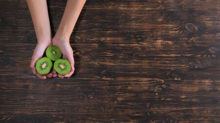 Unrecognizable woman holding fruits over the wooden table. Close up female hands with kiwi Stockfoto