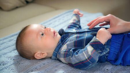 Little baby lying on the blue blanket. Boy kid wearing in shirt and pants. Mother hand stroking the child.
