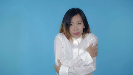 young asian woman posing freezes on blue background in studio. attractive millennial girl wearing white casual shirt looking at the camera Archivio Fotografico