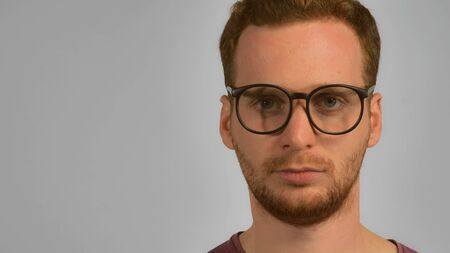close up face caucasian guy with red hair put on eyeglasses. handsome ginger men wearing in casual t-shirt. smart young caucasian man on grey background