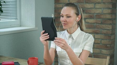 Woman have video chatting with friend on her digital tablet. Sits in the officce by working place
